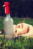 Drunk young woman is sleeping on the grass next to bottle of alcohol in sunny day.
