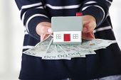 Woman holding PLN ( polish zloty ) bills and house model over white - real estate loan concept