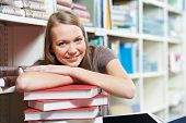 Young pretty smiling woman in a library with books at self-education