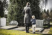 stock photo of funeral  - Woman with little child at the graveyard looking at the gravestone of daddy - JPG