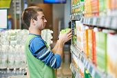 Merchandising. Sales assistant in supermarket lay out goods on supermarket shelves at store