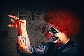 stock photo of clowns  - Scary clown holding large injection needle filled with human vaccine test trials - JPG
