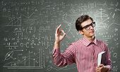 Young funny man in glasses against chalkboard with sketches