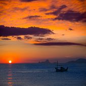 Ibiza sunset Es Vedra view and menorquina fisherboat from Formentera orange sky