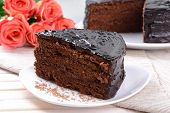 Delicious chocolate cake on plate on table close-up