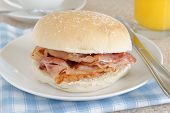 stock photo of bap  - Bacon Sandwich or bacon roll selective focus on the bacon - JPG