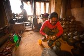 BHAKTAOUR, NEPAL - DEC 7, 2013: Unidentified Nepalese woman working in the her pottery workshop. Mor