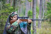 stock photo of backwoods  - Recruit with optical rifle hidden in the backwoods - JPG