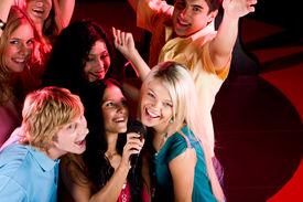 stock photo of karaoke  - Portrait of happy people singing in microphone in the karaoke bar - JPG