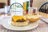 Delicious homemade hamburger with cheese. At the kitchen table.