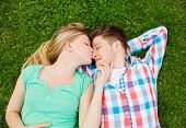 holidays, vacation, love and friendship concept - smiling couple lying on on grass and kissing in pa