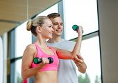 fitness, sport, exercising and diet concept - smiling young woman and personal trainer with dumbbell