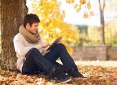 season, technology and people concept - smiling young man with tablet pc computer in autumn park