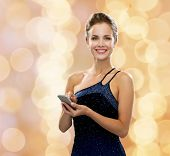 technology, communication and people concept - smiling woman in evening dress holding smartphone ove