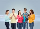 friendship, technology and people concept - group of serious teenagers with smartphones over gray ba