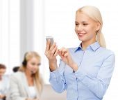 business, technology, service and education concept - smiling young businesswoman with smartphone in