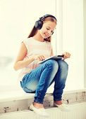 home, leisure, new technology, music concept - little girl with tablet pc and headphones at home