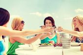summer holidays and vacation concept - girls making a toast in cafe on the beach
