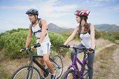 Full length of an athletic couple mountain biking