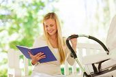 family, child, leisure, education and parenthood concept - happy mother with baby stroller reading b