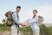 Portrait of hiking young couple holding hands on mountain terrain