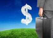 Businessman holding briefcase against cloud dollar