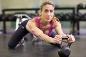 Portrait of a serious young woman lifting kettle bell in the gym