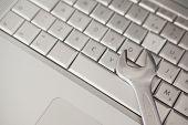 Pliers lying on silver keyboard in office