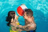 Cheerful young couple playing in swimming pool