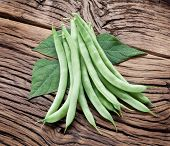 Fresh green beans on the old wooden table.