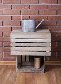 Rectangular wooden boxes on the floor in front of brick wall with watering can and rope