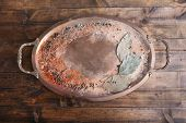 Metal round tray with handles with scattered seasoning and bay leaves on wooden background