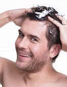 Close-up portrait young happy smiling man washing hair with shampoo - isolated on white.