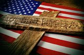 the sentence we do not forget you carved on a wooden cross over the flag of the United States