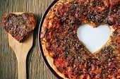 closeup of a barbecue pizza with a heart-shaped cutout on a rustic wooden table
