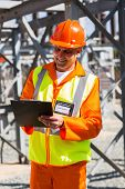 senior industrial technician taking readings in power plant