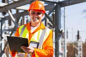 handsome middle aged electrician holding clipboard in electricity power plant