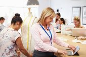 Teacher Helping College Students Studying Fashion And Design