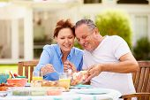 Senior Couple Enjoying Meal In Garden Together