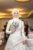 Muslim bride posing with bouquet at a celebration ceremony