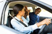 cheerful young african learner driver and driving instructor high five
