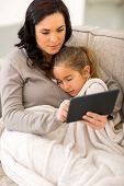 beautiful young woman using tablet computer while her daughter sleeping