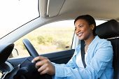 beautiful young african woman driving a car