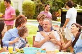 stock photo of multi-generation  - Multi Generation Family Enjoying Meal In Garden Together - JPG