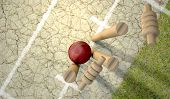 stock photo of cricket  - A red leather cricket ball hitting wooden cricket wickets on a grass cricket pitch background - JPG