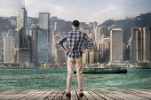 Asian man standing and looking the skyline of the city, Hong kong, Asia.