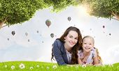 Happy mother with daughter sitting on green grass