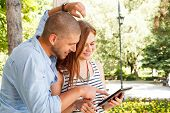Young Couple Using A Tablet Pc In The Park