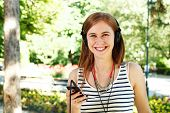 Young Woman Listening To Music With Headphones Via Smart Phone
