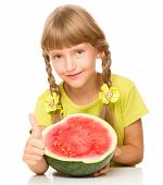 Cute little girl is eating watermelon and showing thumb up sign, isolated over white